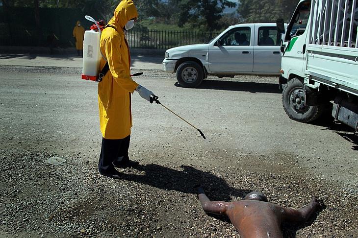Работник министерства здравоохранения опрыскивает специальным раствором тело умершего от холеры человека