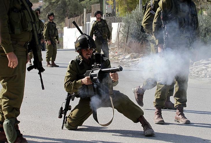 Израильский солдат пускает слезоточивый газ в сторону палестинцев