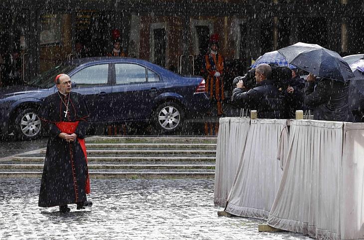 Кардинал идет под дождем во время перерыва в заседании с Папой Бенедиктом XVI в Ватикане
