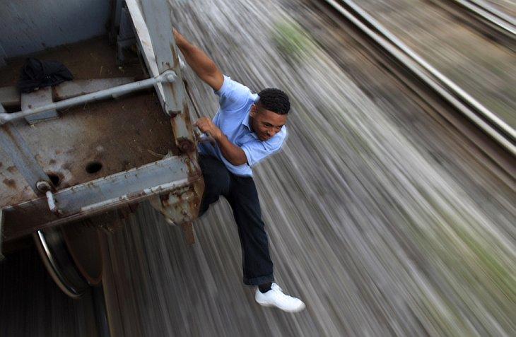 Гондурасский иммигрант Хосе Умберто Кастро, 26 лет, держится на грузовом поезде в Орисаба, Мексика