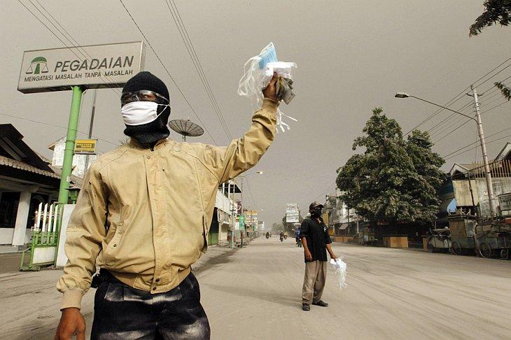 Человек продает маски на покрытой пеплом улице от извержения вулкана Мерапи
