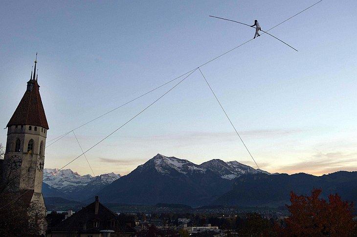 Фредди Нок идет по тросу между замком и церковью в городе Тун, Швейцария