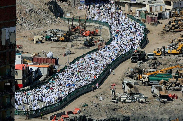 Мусульманские паломники проходят мимо строительство за пределами Большой мечети во время ежегодного хаджа в Мекку, Саудовская Аравия на Пятницу, 12 ноября 2010.