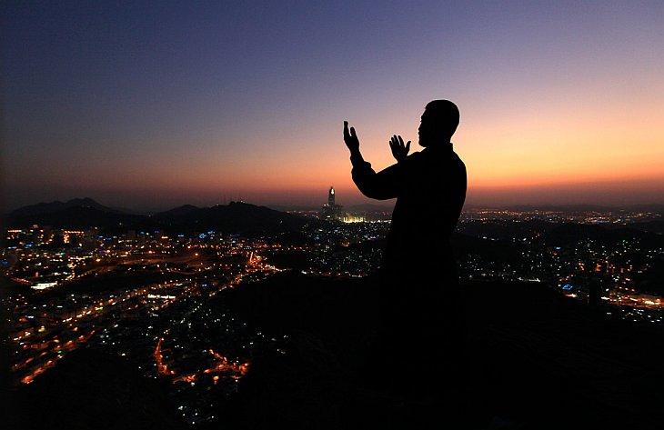 Мусульманский паломник молится в вершине горы Нур
