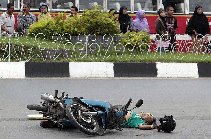 Люди смотрят на тело тайской человека, застреленного повстанцами