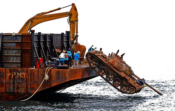 Рабочие сталкивают старый танк с корабля в море