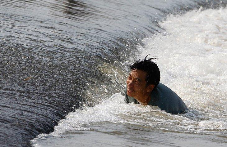 Человек пытается поймать рыбу на затопленной территории в провинции Лопбури