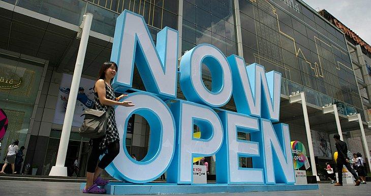 Женщина фотографируется на фоне гигантских букв «Мы открылись» около Центрального универсального магазина в Бангкоке