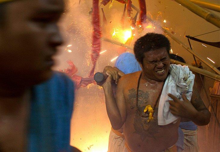 Верующие несут Китайского бога на паланкине на фоне взрывающихся рядом фейерверков