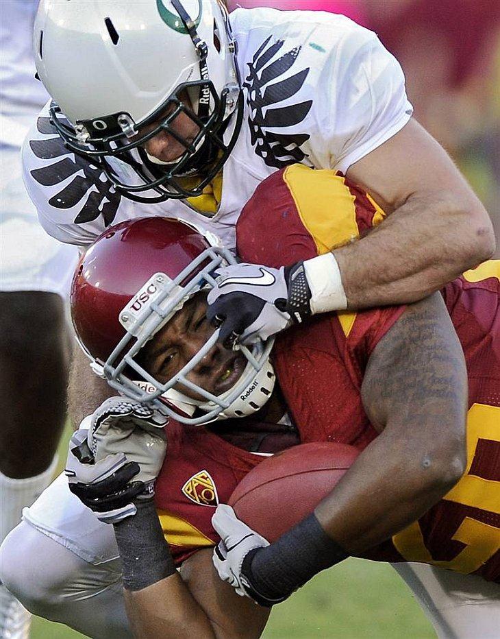Игрок Южной Калифорнии Марк Тайлер (внизу) атакован защитником Орегона Джоном Бойеттом