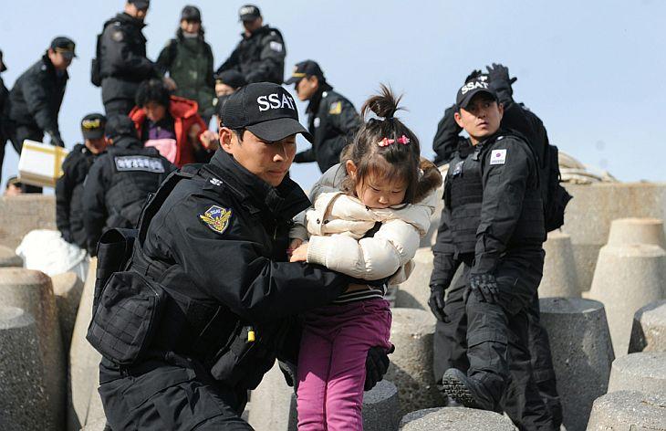 Члены южнокорейской береговой охраны эвакуируют жителей с южнокорейского острова Енпхендо