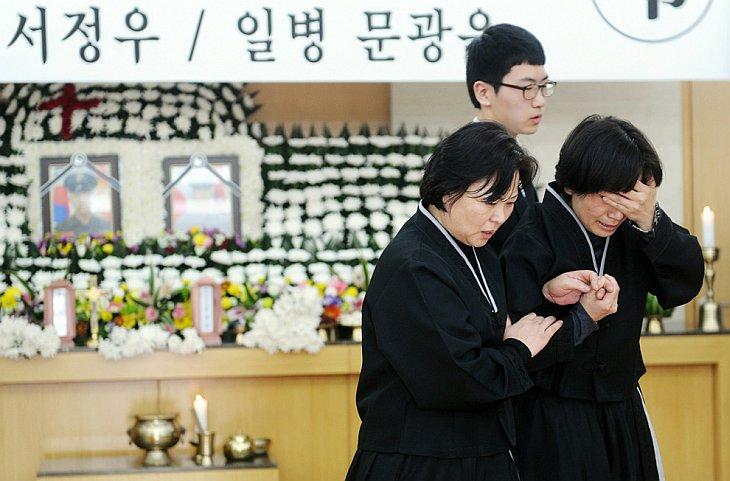Мать погибшего южнокорейского морского пехотинца (справа), который был убит во время нападения Северной Кореи на остров Енпхендо