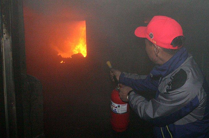 Местный житель пытается потушить пожар с своем доме, 24 ноября 2010, остров Енпхендо, Южная Корея