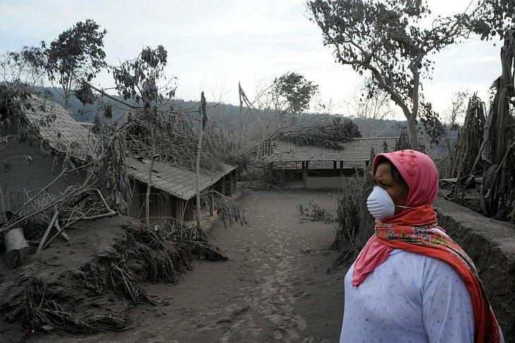 Женщина в маске осматривает свой дом в деревне Калиадем