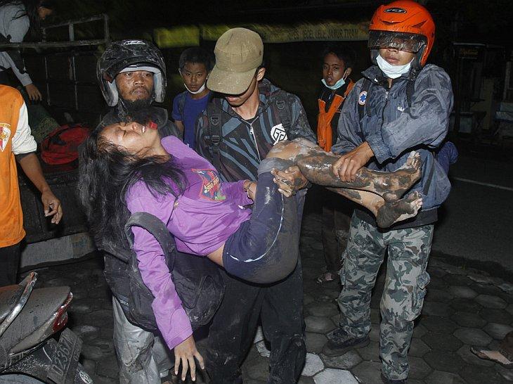 Жители, покинувшие свои дома, несут женщину после очередного извержения вулкана Мерапи в городе Klaten