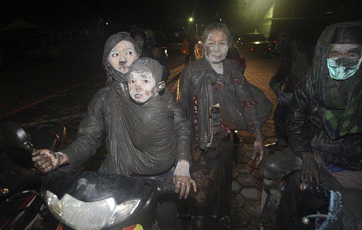 Жители покидают свои дома на мотоциклах после очередного извержения вулкана Мерапи в Клатене, Индонезия