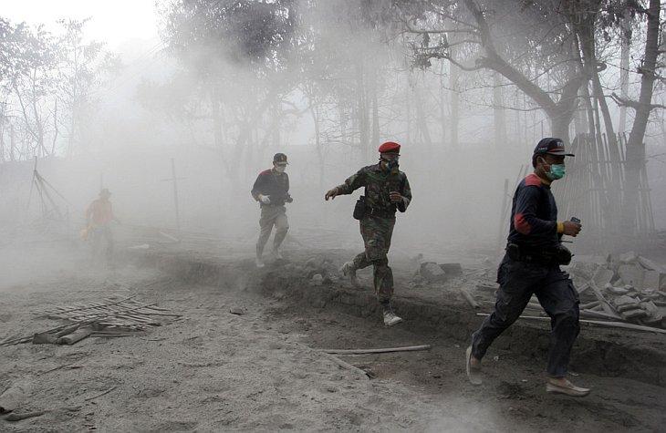 Индонезийские солдаты и спасатели бегут после извержения вулкана Мерапи