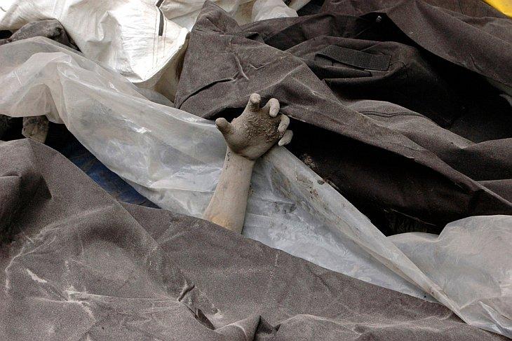 Рука жертвы извержения вулкана Мерапи видна среди мешков с телами городском морге