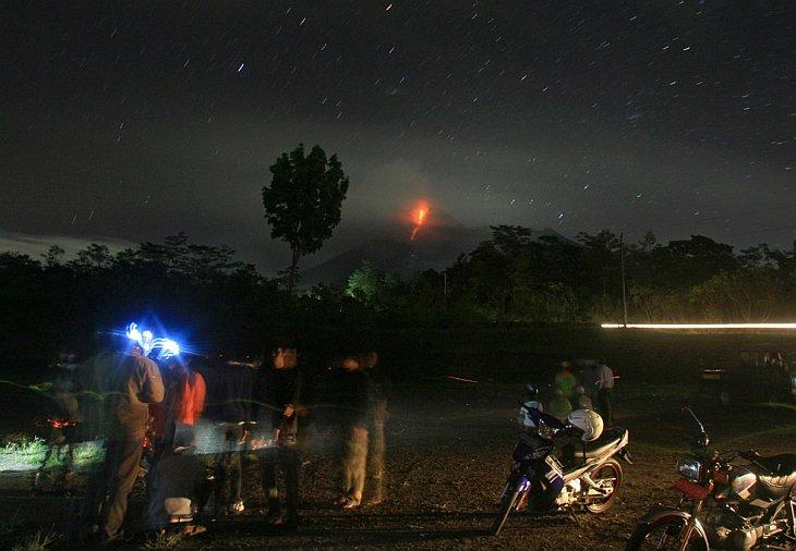 Люди смотрят, как вулкан Мерапи извергает вулканические материалы
