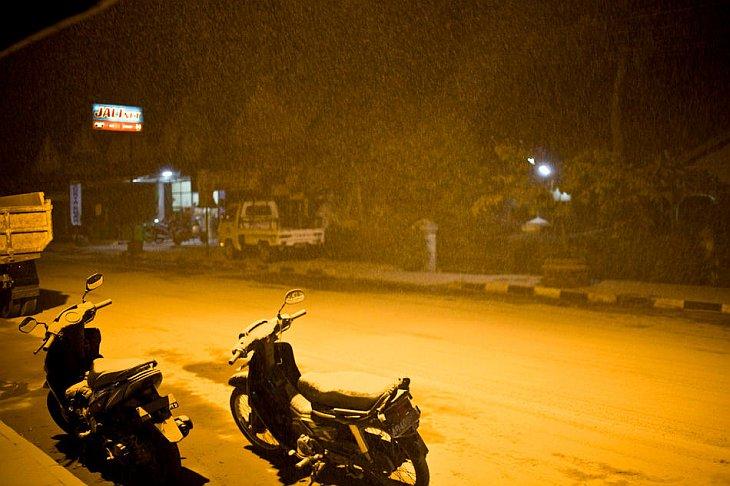 Мотоциклы, покрытые пеплом от вулкана Мерами, стоят на улице города Джокьякарта