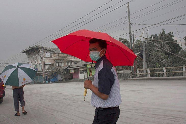 Человек идет по улице, покрытой вулканическим пеплом от извержения вулкана Мерапи