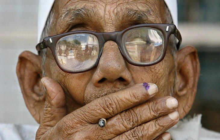 Пожилой человек курит на улице у избирательного участка в городе Варанаси в северо-восточной Индии