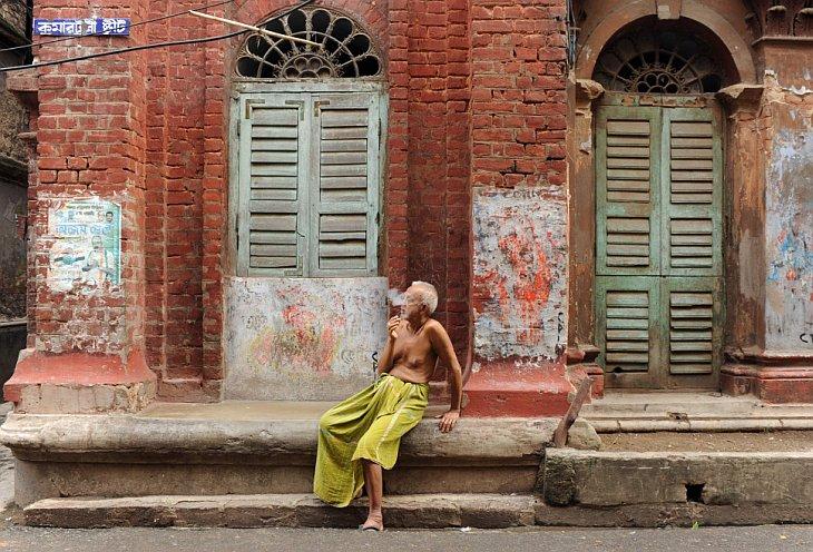 Пожилой индиец курит на улице в городе Калькутта, Индия