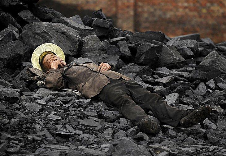 Китаец курит в отвале для золы и шлака, Чанжи, провинция Шаньси, Китай