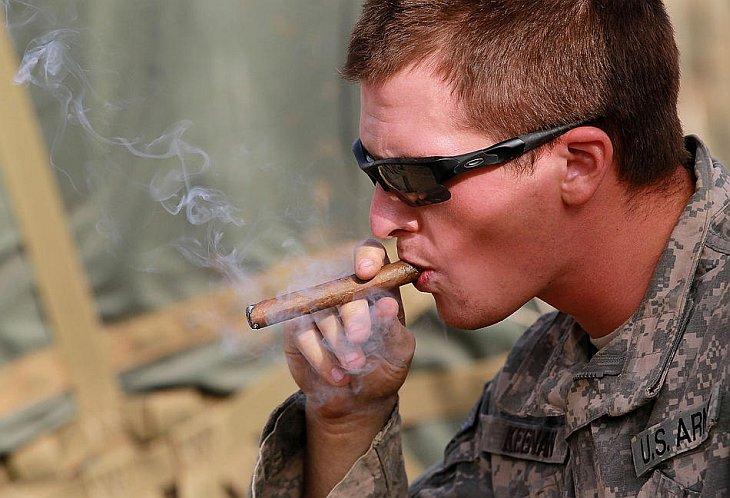 Лейтенант американской армии Том Кинан из Нью-Йорка курит сигару