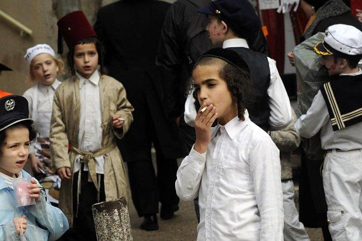 Еврейский мальчик курит на празднике Пурим в Иерусалиме