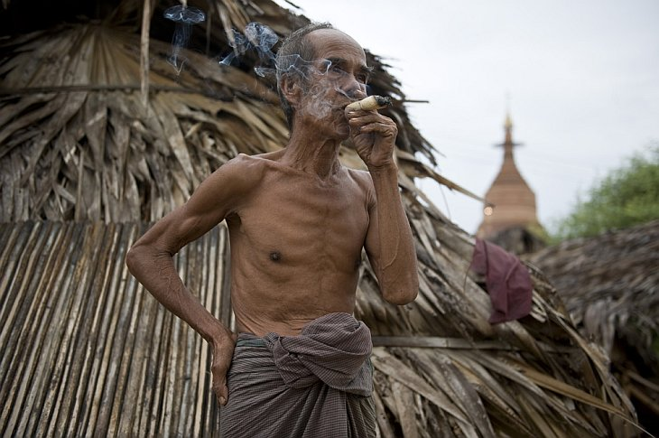 Старик курит сигару местного производства в Мьянме