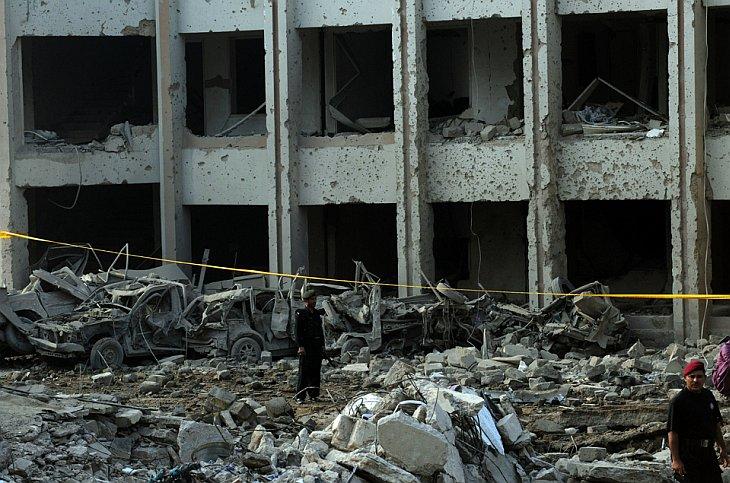 Пакистанские полицейские охраняют остатки здания в Карачи после ночного взрыва бомбы