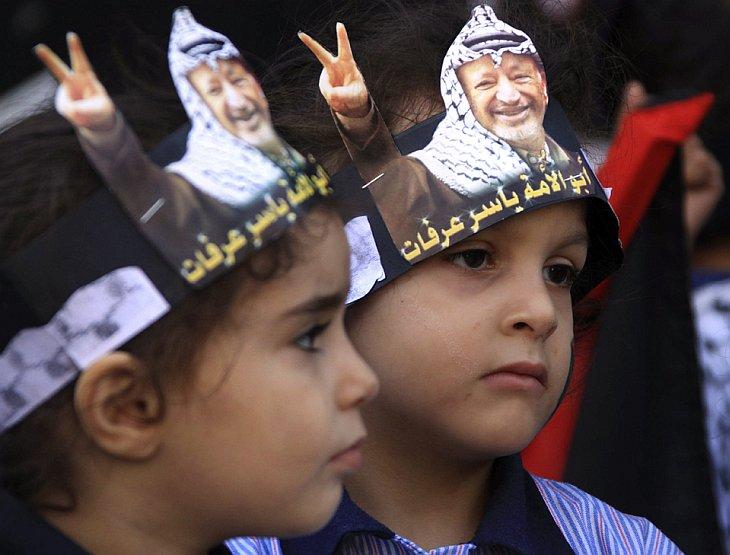 Палестинские дети с бумажными кронами с изображением покойного лидера Ясира Арафата