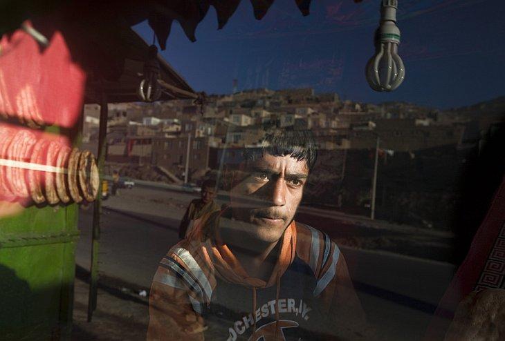 Сотрудник пекарни смотрит в окно, ожидая покупателей в Кабуле, Афганистан