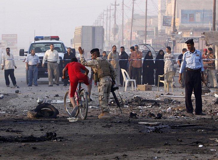 Иракский солдат прогоняет велосипедиста с места взрыва машины возле ресторана в Басре