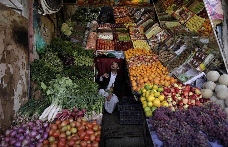 Человек сидит среди фруктов и овощей в своем магазине в Сане