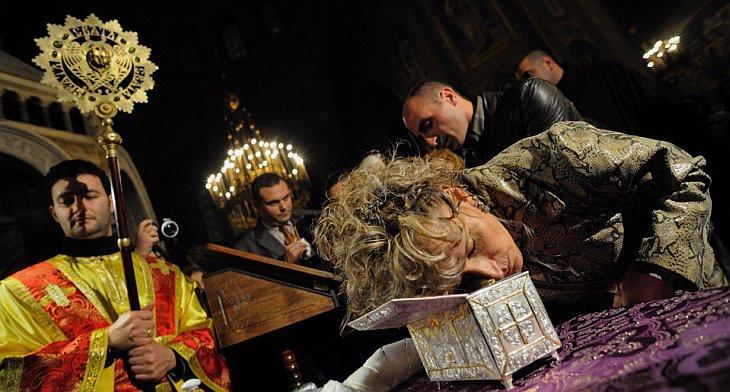 Болгарская верующая целует окно, содержащее мощи Иоанна Крестителя в соборе Александра Невского в Софии