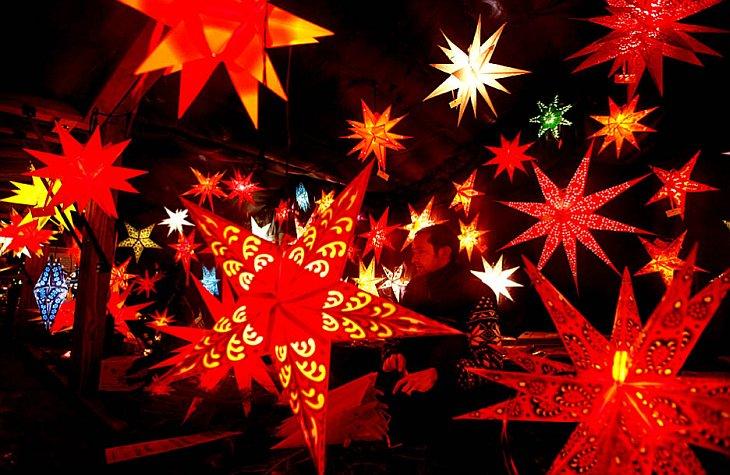 Продавец разноцветных звезд ждет покупателей на Рождественской ярмарке на площади Александрплац в Берлине