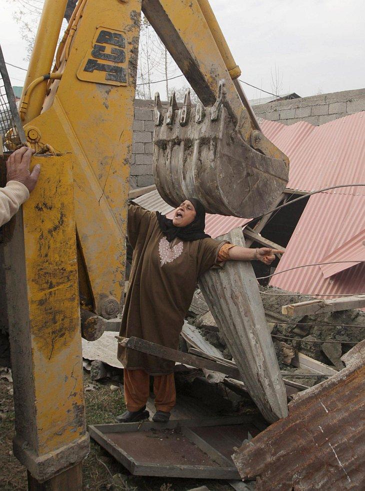 Женщина пытается остановить бульдозер, сносящий ее незаконную постройку в Сринагар, Индия