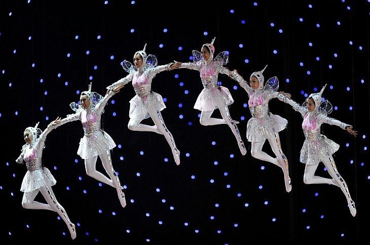 Исполнительницы парят над сценой во время церемонии закрытия World Expo 2010