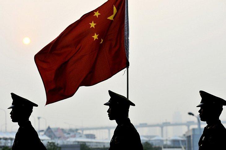 Китайские солдаты проходят мимо китайского флага на World Expo 2010