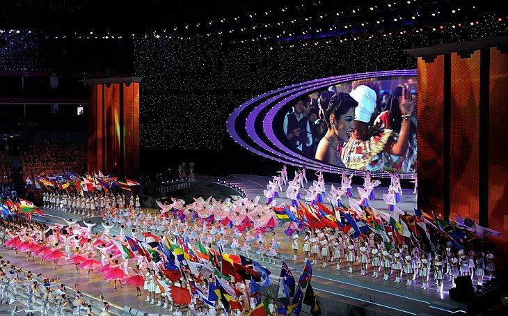 Исполнители махают флагами во время церемонии закрытия World Expo 2010