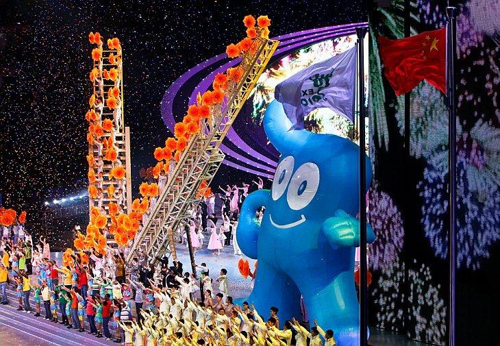 Китайские и иностранные исполнители танцуют на фоне талисмана World Expo 2010
