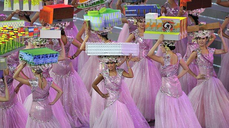 Исполнительницы маршируют со шляпами в виде павильонов