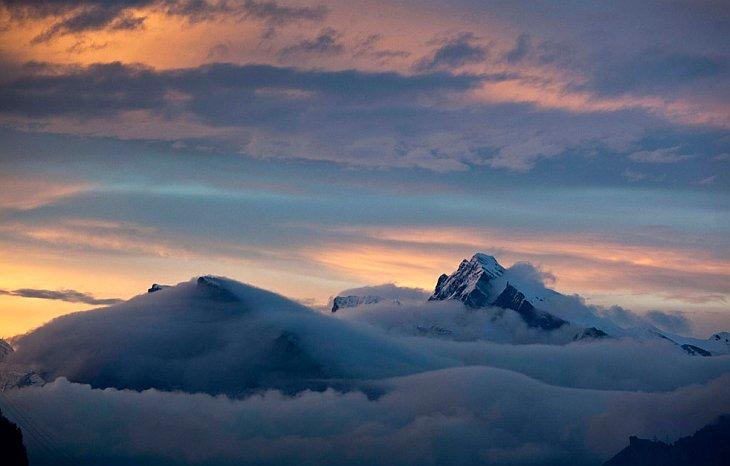 Вершины гор появляются из облаков, недалеко от города Игис, Швейцария