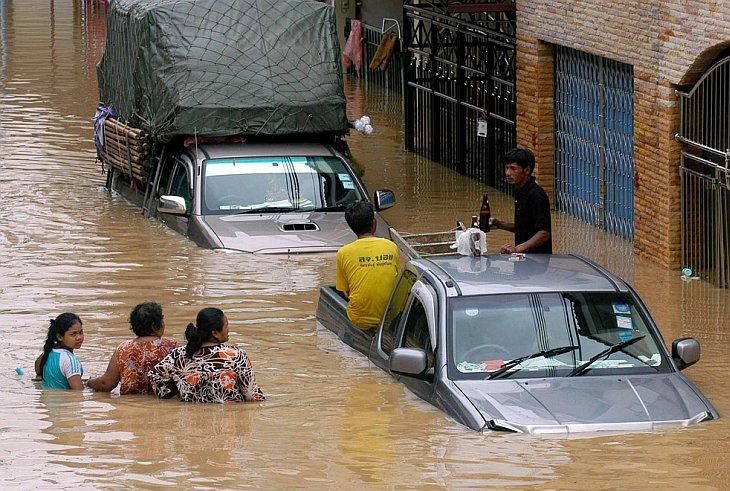 Жители пробираются через паводковое наводнение в центре города Хат-Яй на юге Таиланда