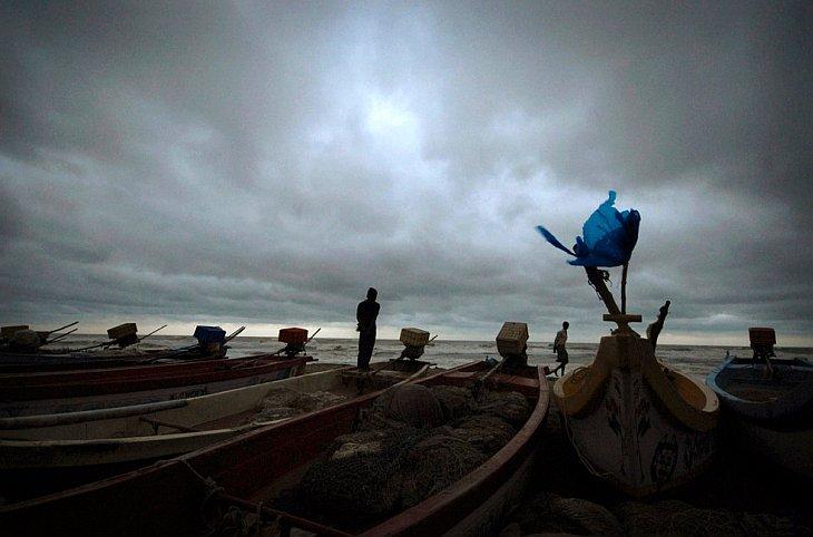 Индийские рыбаки смотрят на Бенгальский залив, штат Андхра-Прадеш