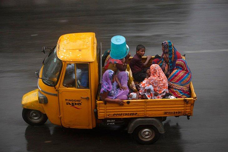 Индийские женщины и дети едут в пикапе во время сильного дождя в городе Хайдарабаде, Индия