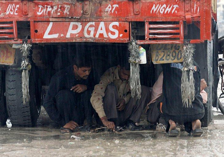 Индийские рабочие прячутся под грузовиком от дождя в Нью-Дели