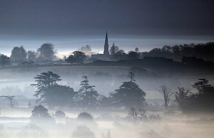 Зимнее солнце начинает подниматься над туманом, который стелется над полями 15 ноября 2010 года недалеко от города Гластонбери